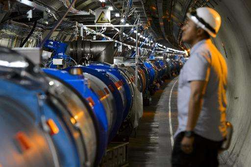 A scientist looks at a section of the Large Hadron Collider (LHC) which was used to prove the existence of the Higgs Boson—also