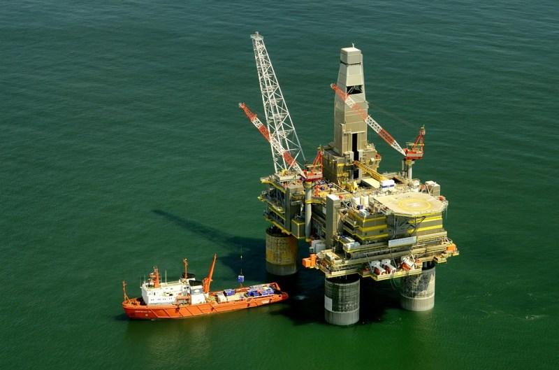 [Na imagem uma plataforma de extração petrolífera. | Texto: Descubra o que são e como investir em commodities - Positive Company