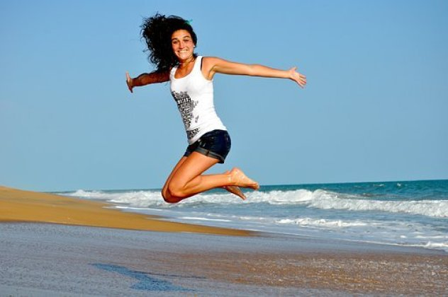 Happiness hormones and how to produce them naturally depicted by a woman in blue shorts jumping at a sea shore