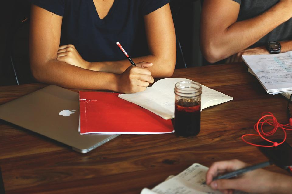 People sitting at a table with notebooks and pens, writing. There is a glass of pop (soda) in the centre and a macbook at the left edge. On the right there is a tangle of red headphones.