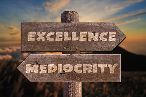 An image of a sign that points one way to mediocrity and one way to excellence.