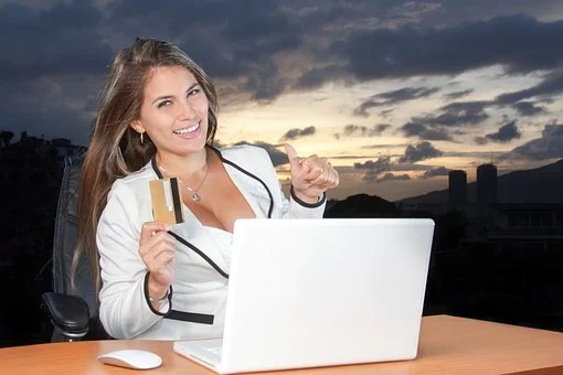 Ecstatic lady in white holding a credit card and sitting behind a table with a laptop before her