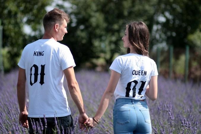 un ragazzo con una maglietta bianca con scritto KING e 01 in caratteri gotici, tiene per mano una ragazza con una t -shirt bianca con scritto QUEEN con lo stesso stile. Di spalle camminano in un campo di lavanda