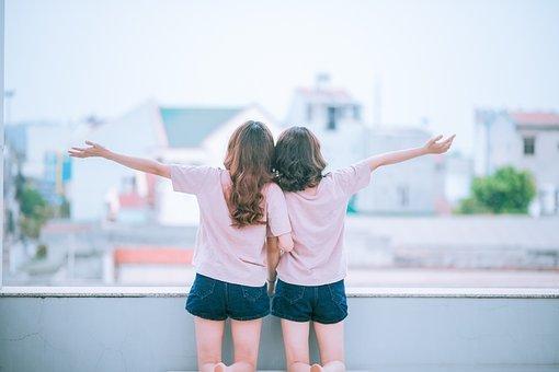 Due ragazze di spalle affacciate ad un balcone a si tengono sottobraccio al centro e hanno l'altro braccio allargato. Indossano lo stesso completo t-shirt rosa e pantaloncini corti di denim.