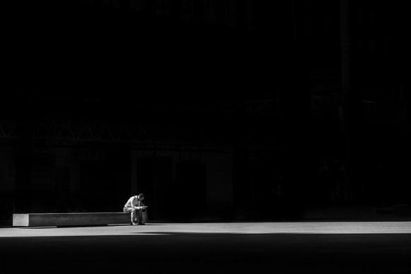 Un hombre sentado solo en un enorme banco de hormigón sobre una explanada de hormigón sobre un fondo negro. (https://i2.wp.com/cdn.pixabay.com/photo/2016/11/23/15/31/man-1853545_960_720.jpg?resize=582%2C388&ssl=1) (https://pixabay.com/es/users/pexels-2286921/)