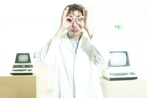 A man in a mocking mood stanidng with rounded fingers around eyes between two computers