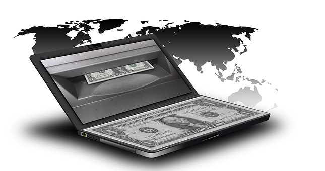 Dollar bill falling out of the top of a laptop computer like paper coming out of a printer to signify earn money