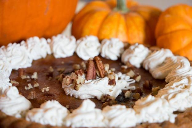 pumpkin pie with pumpkins in the background
