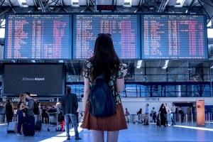 Jeune femme devant un panneau d'affichage d'une gare