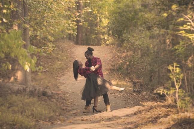 Una coppia in mezzo ad un sentiero nel bosco fanno un caschè e si guardano negli occhi. Lui indossa una camicia a scacchi rossi e neri con jeans scuri, lei indossa la stessa camicia annodata in vita con una gonna di tulle nera e scarpe decolletè nere.