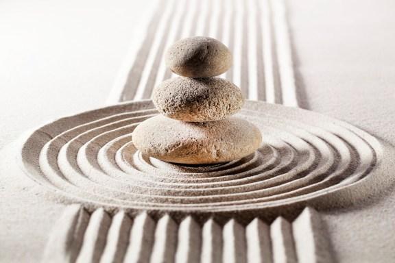 zen stones stacked in sand