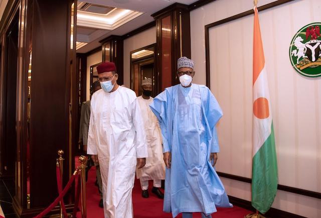 Buhari, right, leads his Nigerien guest Bazoum to dinner