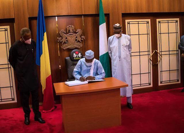 Deby signing the visitors register for the last time. Left is Nigeria's foreign minister Geoffrey Onyeama