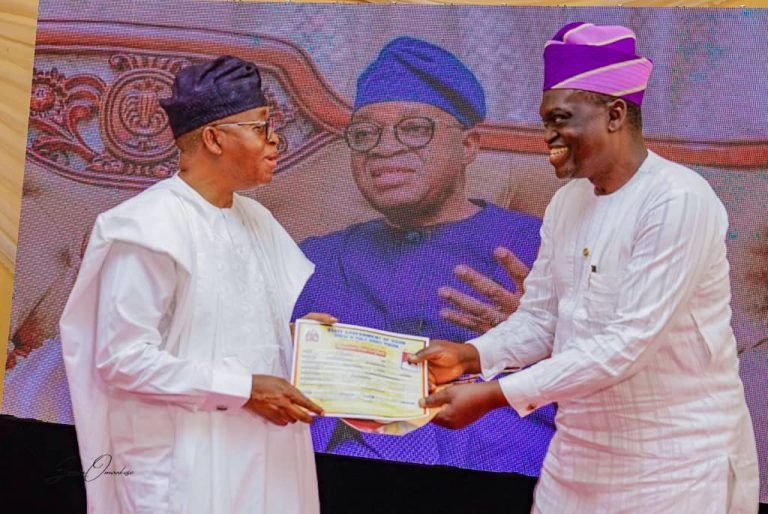 Gov. Oyetola presents a bond certificate to one of the Osun  retirees
