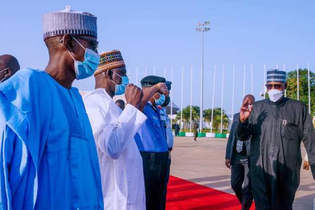 President Buhari greets some of his aides before boarding the plane
