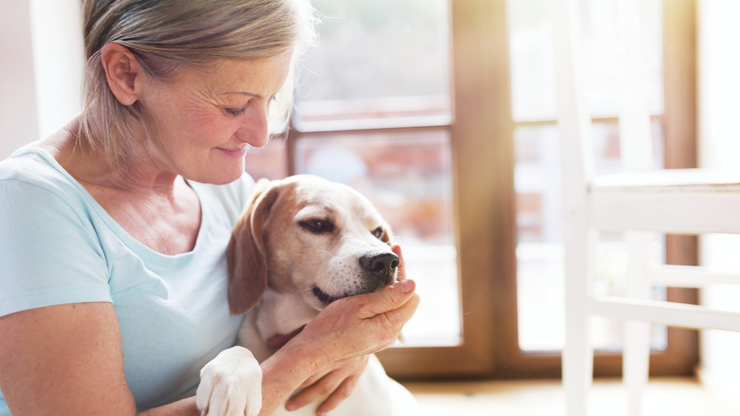 a woman holding and petting her dog