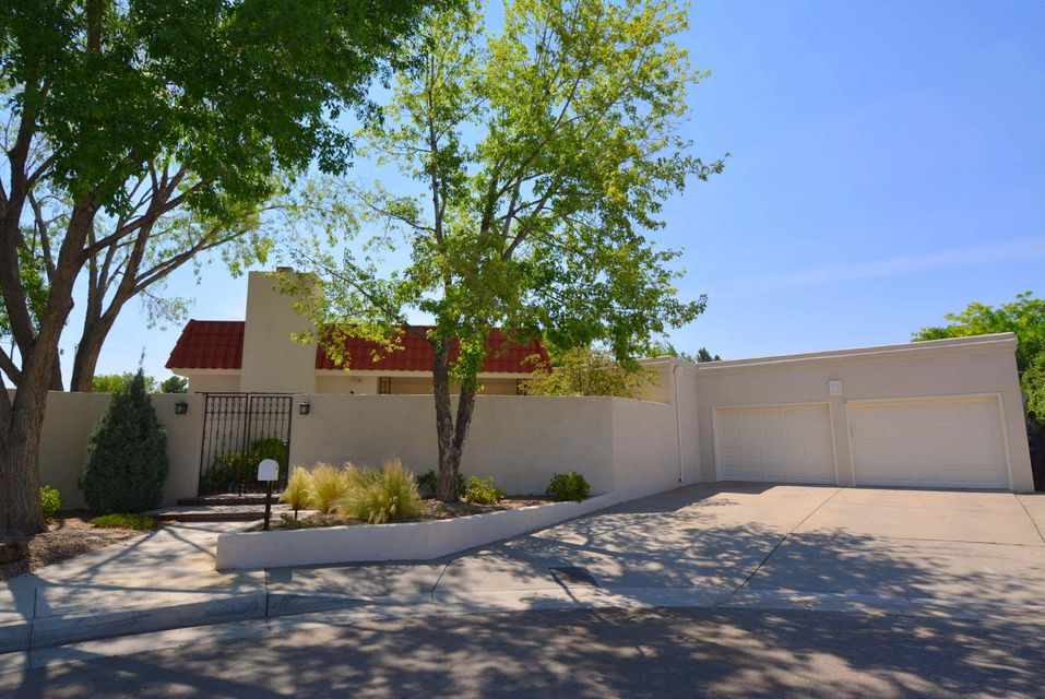 Exquisite finishes abound in this very private Mossman on two lots.  Formal living, dining and entry have classic moldings ceiling to floor & a magnificent crystal chandelier.  Hardwood parquet flooring in hallways and living areas.  A separate den features wet bar, plantation shutters, marble fireplace, large windows & views of the formal garden.  White kitchen with black & grey accents includes 30' of counter space, double ovens, double sinks, 40 cabinets & drawers plus large, eat-in dining.  Master looks out to private patio & has 18x12 walk-in closet (cedar lined), large bathroom with sunken marble tub, shower & bidet.  New stucco, 1 yr. old roof/skylights & 3 yr. old heating & air units.  Lge patio & garden room make this home great for entertaining indoors or out.Tanoan alternative.