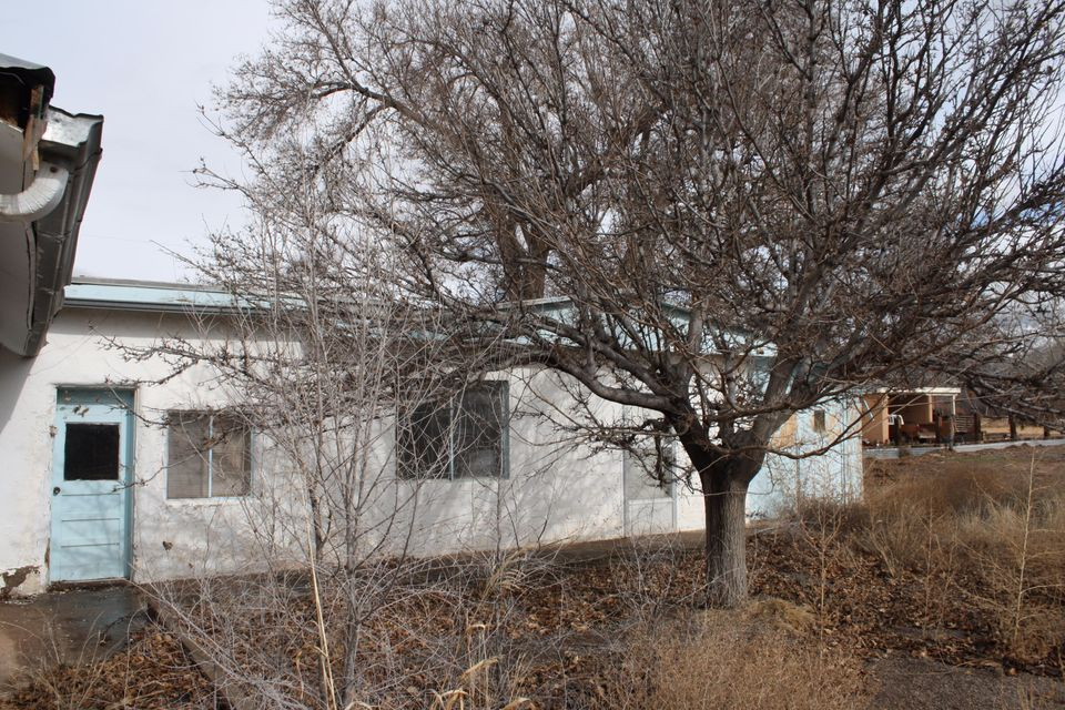 Purchase a piece of Great History and excitement in the beautiful Village of Corrales. One Acre Lot right on Main Street! Home sold AS IS, work needed, waiting to be reconstructed or demolished and rebuild! Older part of home has thick adobe walls! Fabulous View of Sandia Mountains! Seller will consider REC real estate contract. VALUE IS IN THE LAND!On the old camino rael and close to Historic San Ysidro Church