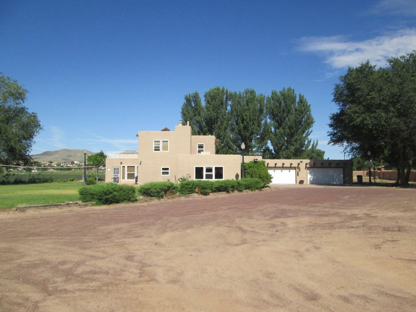 Executive custom Pueblo-style adobe on 1.5 acres! Designed for entertaining. Features include exposed adobe walls, rough hewn beams, tile and parquet floors. Huge country gourmet kitchen with lots of counter/cabinet space, large work island & breakfast bar. Sunroom has brick floors, HW baseboard heat. Massive upstairs Master Suite with view deck. Master Bath has jetted tub/separate shower & double sink vanities. City water, city sewer & irrigation well for water grass & plants. Fabulous location convenient to I-25 & Albuquerque & close to shopping, schools, Walmart, theater & everything you need!