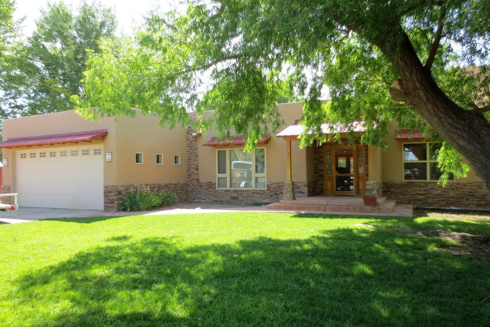 Beautiful north valley home that is a car collector's dream! 4,097 s.f. w/ a detached 2,000 s.f. 8-car garage. Located on an acre that backs up to the Bosque and Rio Grande State Park. Home was extensively remodeled and doubled in size since it was built in 1962. Fresh paint, radiant heat floors, solar panels, Trane HVAC units, newer windows, granite counters in baths, Master bdrm has deck w/ CalSpa hot tub, views of the bosque. Master bath has Kohler body spa and Davis custom cabinets. Security system for both house and garage. Roof has life-time warranty. Auto-security gate to back yard. Detached garage w/ 5 show bays & 3 work bays, acrylic floors, built-in storage cabinets, its own HVAC, plumbing and 1/2 bath, awning for shade at exterior wash bay. If you don't have that many cars or