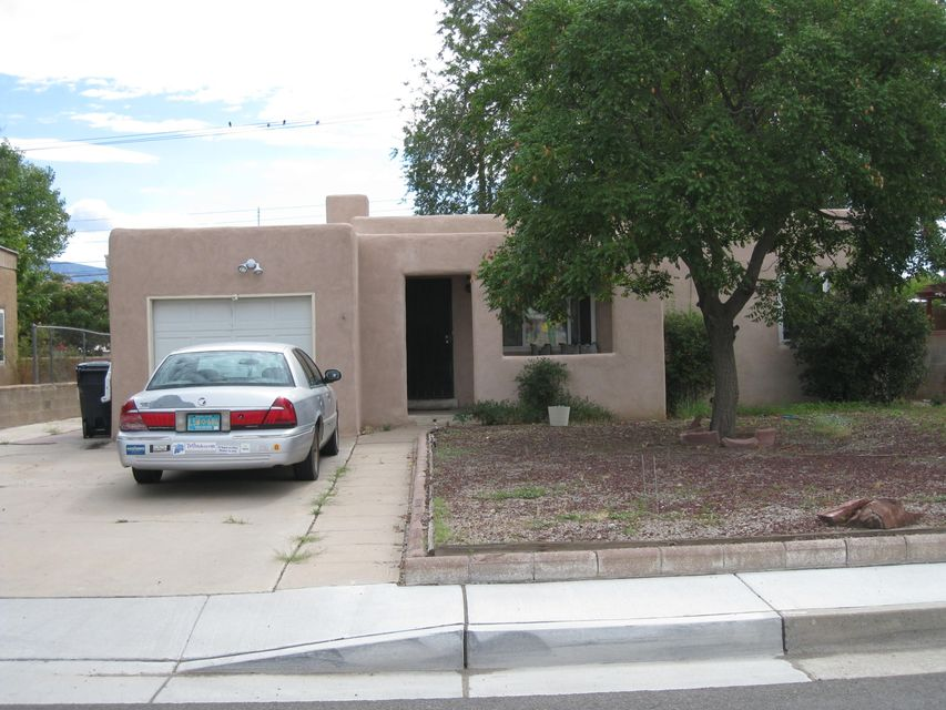 Across from Whitier Elementary, Close to UNM. Lots of Potential with this house, Open Floor Plan, 12 x 27 add on in back of house.  Old but usable storage shed on property. Hardwood Floors, Updated Windows.  Insulated Garage.