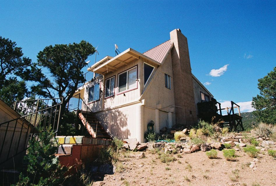 This is a unique lot with extraordinary 360 degree, unobstructed views of the City and Sandia Mountains. This is, topographically, perhaps the highest home in the Albuquerque area and comprises 2.38 acres which potentially can be subdivided into three lots. Make this 1,200 sq. ft. home your getaway from the City below or build your dream home and use the existing home as a guest casita and artist studio. Close to the La Luz and Piedra Lisa trails in this secluded, beautiful Evergreen Hills location. Outstanding possibilities!