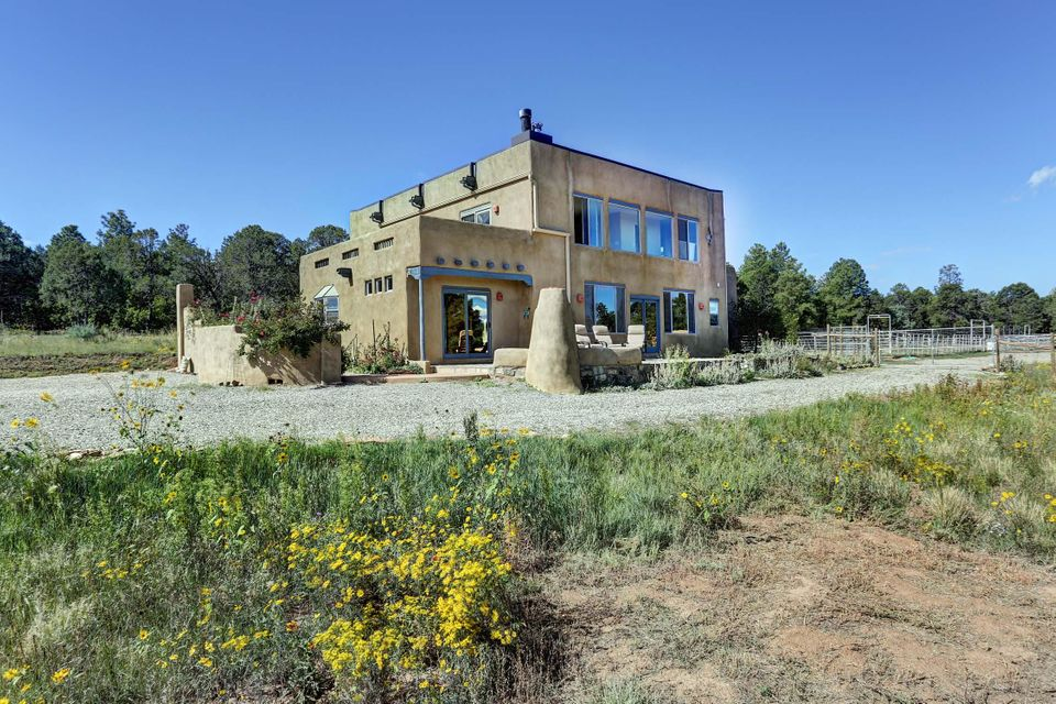 Country living at its finest, only 30 minutes away from Albuquerque! Come see the 100 foot pines, stars like you've never seen, and not another house in sight! Windows, windows, windows... true indoor/outdoor living in this custom, 3,324 SF beauty with non-stop views. Bring all your critters; 6.37 usable acres, custom 3 stall barn, pipe fenced turnouts, barn master stalls, hay storage, 100x80ft arena, fenced for pasture rotation. Dog fenced 1/2 acre. Fully insulated, 4 car garage, with tons of cabinets for all the toys. Gorgeous additional 495 SF guest house for the in-laws. 50 miles of Forest Service trails 5 miles away. This is where ABQ comes to play! Open floor plan, large rooms and 2 custom fireplaces.  Brand new TPO roof with transferable warranty.
