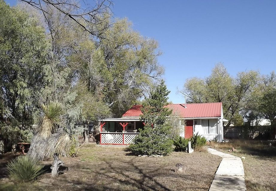 Estancia, New Mexico cottage home for sale.  This cute 1 bedroom older home on two city lots is  perfect for an individual or couple. The Central NM, Torrance County home has mature trees, is fully fenced yard, has a covered patio and a shop/garden shed.  The home is in need of some updating, but has many possibilities. The living room has a lovely hardwood floor that is in good condition. Less than an hour to Albuquerque and about 75 minutes to Santa Fe.
