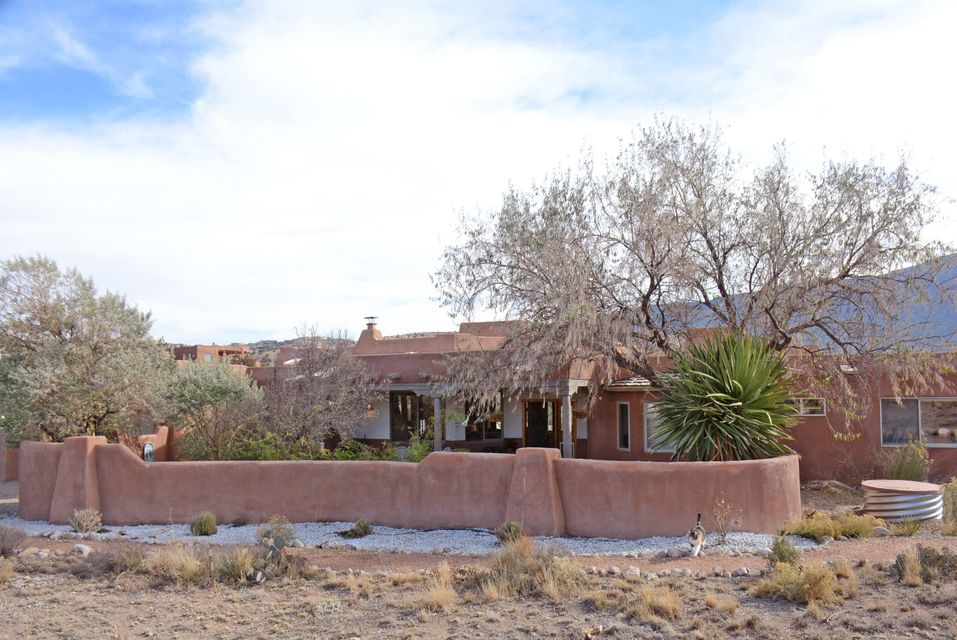 Marvelous Mountain Views! Lovely Tom Ashe home with lots of Southwestern Flair. Exposed adobe walls, Vigas, Corbels, Beam Ceilings, slate, ceramic and carpeted floors. Wood panel doors,6 skylights (2 in garage),Formal D/R, Sunken L/R, 3 kiva fireplaces! Fabulous, spacious Master Ensuite w/Kiva FP. Courtyard Entry with hand crafted gate, decking in back.  TPO Membrane Roof 2016. Community water system and natural gas. Anderson windows replaced in 2015. Recirculating pump.