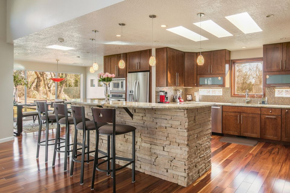Impeccably updated, one level custom home on a lush, landscaped acre in the N Valley.  High ceilings, Open Kitchen w/ tall Island breakfast bar, granite tops, custom cabinets, and tons of natural light! SS appliances, wine fridge, butler's pantry, wine storage, and family dining w/ Mountain views too! There's a family room with a magnificent stacked stone fireplace, office, formal living room, study, luxurious master suite, 2 guest rooms, updated baths. Awesome outdoor living! The yard is great for parties, football/soccer games etc! Everything is on private well, so no water bills! Ref. air also.  Gorgeous wood, travertine tile, & plush carpet throughout. LOCATION! Easy access to shopping, restaurants, movies, Paseo, etc. w/ direct access to Bosque, bike trails in the neighborhood
