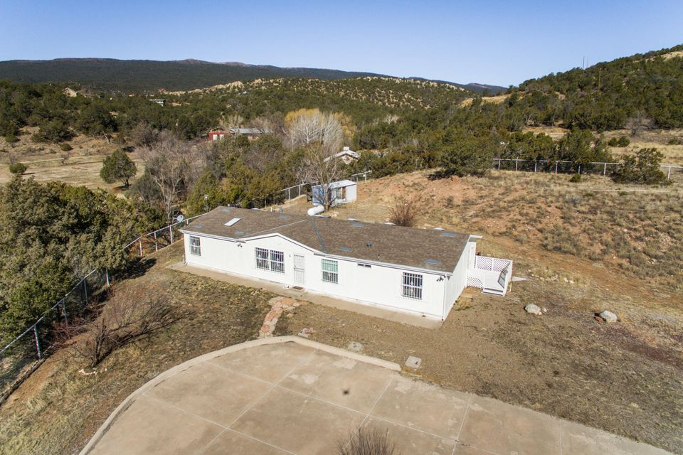 OPPORTUNITY to own a piece of Mountain Tranquility while only 8 min to Albuquerque. 2.3 acres with trees, equipped with irrigation well and CITY WATER. 4BR/2BA well maintained home needing a few updates. Vaulted Ceilings, skylights, Formal Liv Area, Spacious Greatrm/Den ,So much light with open floor plan, Plenty Of Kitchen Cabinetry,Pantry,Breakfast Bar/Nook,Utility room for WATER SOFTENER and W/D, Large Master Ste,Private Bath W/Garden Tub/Sep Shwr, 4th Additional Bedrm/Office could be INLAW quarters with separate entrance. Property can be subdivided, Wonderful Horse property Make it your own...