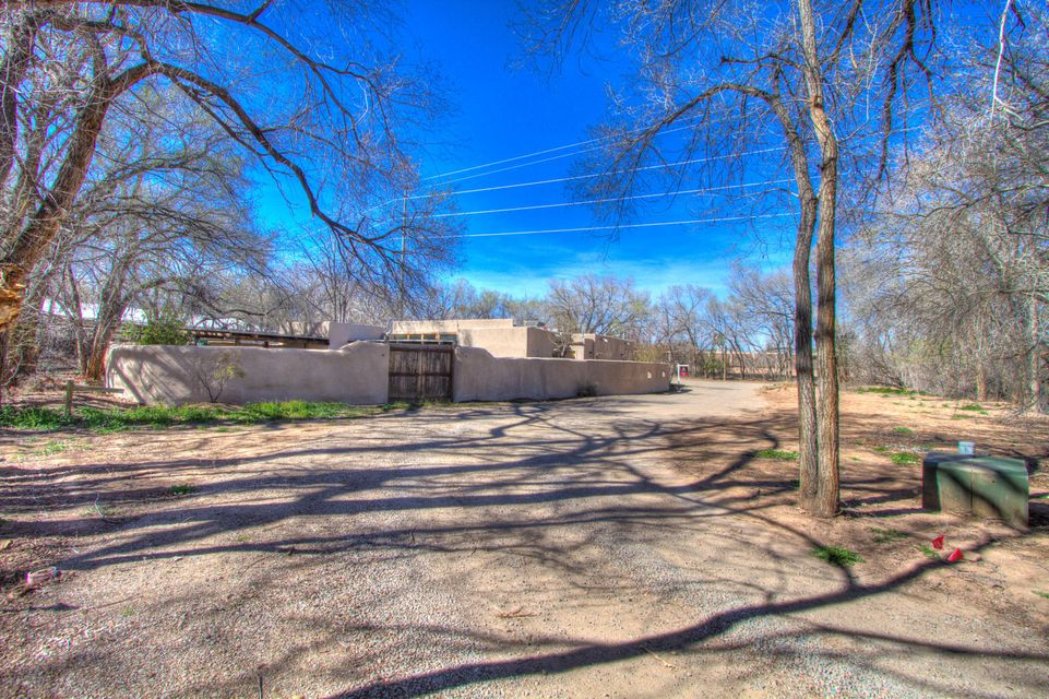 Stunning single story Adobe home in North Valley. This spacious estate is situated on just over an acre. Fully enclosed adobe wall in ground gunite pool.4 bedrooms 4 full baths and 2 half baths. Open light and bright 5 custom Kiva fireplaces. Spacious bedrooms all have their own baths. This home would be great for multi generational families, or bed and breakfast. Big game room or man cave extra spacious 5th bedroom or office. This home is a must see.Seller will build wall or large garage with acceptable offer