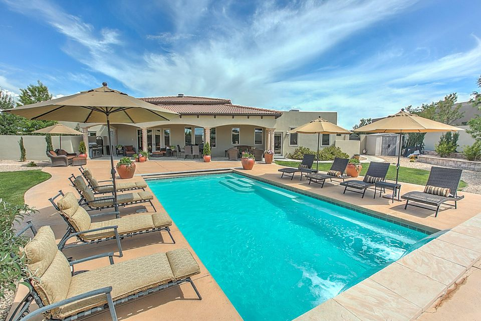 Now $599,000 so take another look. This dream home and resort style backyard features a heated pool with a waterfall, gas fire pit, and covered patios.  The home is designed to dazzle with rich finishes including barrel ceilings, variance plaster, Mexican Noce' tile, and hand hewn hickory wood floors.  The chef's kitchen is a dream with top notch appliances,  3 sinks, granite counter tops, and custom Craig Sower cabinets.  This open concept floor plan is completed by a great room, formal dining room, 3 guest bedrooms, and master suite.  The master suite has it all with an exercise room, gas two-way fireplace, large soaking tub, and private courtyard. Located in central Rio Rancho there is quick access to Hwy 528 and Unser.  This home is sure to please all who enter.