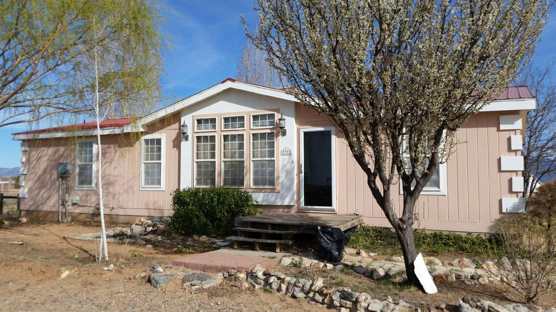 This is a beautiful home for your Family! Spacious double wide, permanent foundation on one full acre.  Lots of sq. ft. for your dollar. Not far east of El Cerro Loop. Has amenities that Buyers are excited to find, family room with fireplace, spacious country kitchen, metal roof, and panoramic views. Hurry to see this home!