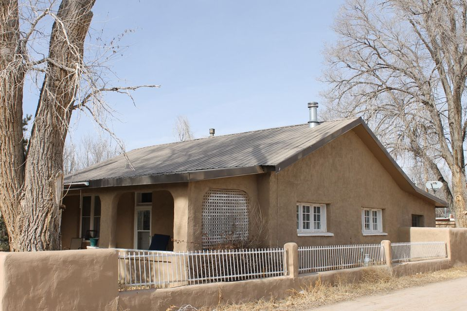 100 Year old , updated adobe with over a century of history conveyed. From the adobe outbuildings to the grand Cottonwood trees, this home conveys an aura that is unique and specific to NM history. Prepare meals in the new, updated kitchen; new plumbing and Kenetico water system, new sewer clean outs and outside frost free faucets. The master bath has been remodeled, featuring a jetted tub and new skylight. Fresh paint and designer accents throughout. Electrical has been updated. This is an amazing property and one of a kind property.