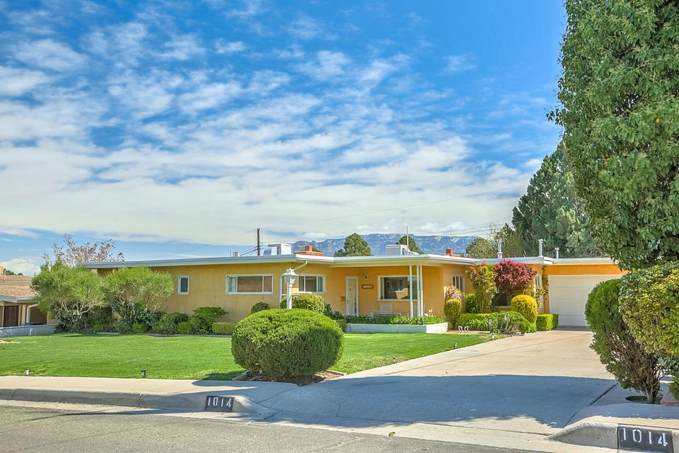 Welcome Home to this incredible revitalized destination neighborhood!  Dream, close-in location- Smith Sandia Hills and all it has to offer! Great schools, excptnl I-40 access, UNM/Nob Hill/Altura Park/Whole Foods. Original owner, lush landscape, views & natural light from sunrise to sunset. Interior ftrs incld newly refurbished hardwood floors, cstm wood paneling & cabinetry, two inviting frplcs, great brick acntng, heated sunroom & more. New carpet & custom vinyl just installed. Mltple living & dining areas incld sun-filled living rm w/cstm frplce, family rm (plumbed for 3rd frplce) plus charming den/office w/frplce complete this versatile flrpln. Outside provides lush lawn, mature landscaping w/private back yard & two storage bldngs. Don't hesitate- see this today! Location, location!!