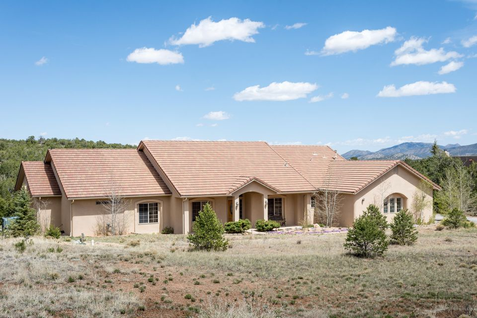 **Priced below appraisal** Come see this beautiful custom home designed by and built for current owner.  This single level home sits on 2.9 wooded acres with privacy and views. The open floor plan is flanked by two master bedrooms with access to the covered patio out back.  The kitchen is lined with stainless steel appliances, corian counter tops, knotty cherry cabinets, and a double convection oven.  Enjoy watching T V and relax to the warmth of the kiva gas log fireplace.  There is a cozy office next to the formal dining room, a  huge master salon bathroom, double walk-in closets, separate shower, and jetted tub.  The two car garage is fully finished with a shined up work space. There are so many extras here you just need to bring your Realtor and see for yourself.