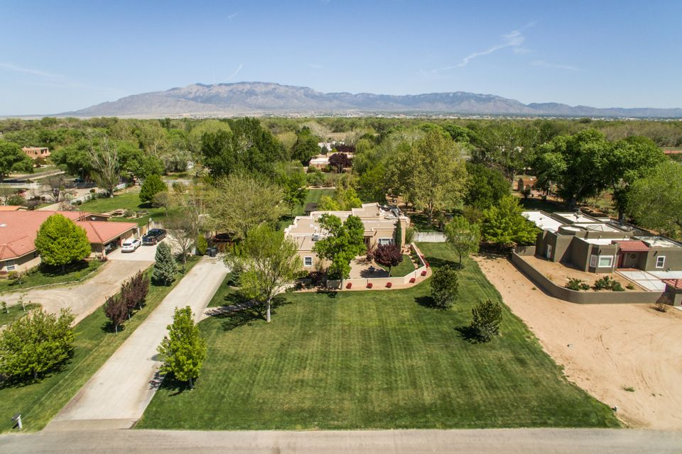 A true Oasis in the desert!  Impeccably updated, one level custom home on a lush, landscaped acre in the N Valley.  High ceilings, Open Kitchen w/ tall Island breakfast bar, granite tops, custom cabinets, and tons of natural light! SS appliances, wine fridge, butler's pantry, wine storage, and family dining w/ Mountain views too! There's a family room with a magnificent stacked stone fireplace, office, formal living room, study, luxurious master suite, 2 guest rooms, updated baths. Everything is on private well, so no water bills! Ref. air also.  Gorgeous wood, travertine tile, & plush carpet throughout. Yard large enough for pool, with a huge, lush lawn! GREAT LOCATION! Easy access to shopping, restaurants, movies, Paseo, etc. w/ direct access to Bosque, bike trails in the neighborhood