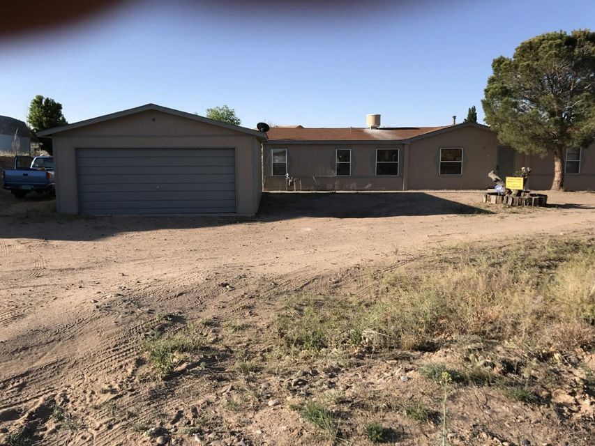 Double wide on a permanent foundation. On over half an acre with views. Only about 2.5 miles east of the intersection of El Cerro and  South 47.  Good looking 3 bedroom 2 bath. Over 1600 square feet plus a detached 400+ square foot 2 car garage. On a nice cul de sac in a quiet  little Los Lunas neighborhood. Fenced back yard, wood burning stove, views.