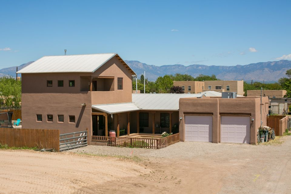 Hard to find Northern New Mexico charmer in the fabulous North Valley. Newer construction in an established neighborhood, on 1/3 of an acre.  Close to Old Town, Downtown, Bosque trails, shopping, dining and entertainment.  Bathed in natural light with an open concept floor plan, high ceilings, kiva fireplace, gleaming hardwood floors, custom Knotty Alder kitchen cabinetry, tons of storage, granite counter tops, large kitchen island and stainless steel appliances. Grand master suite with walk-in closets, his/hers vanities and walk out balcony with panoramic views of the Sandias.  An entertainer's delight awaits in the huge landscaped yard with mature greenery and low maintenance landscaping, covered and open patio, and a huge oversized garage. Visit this lovely home today!