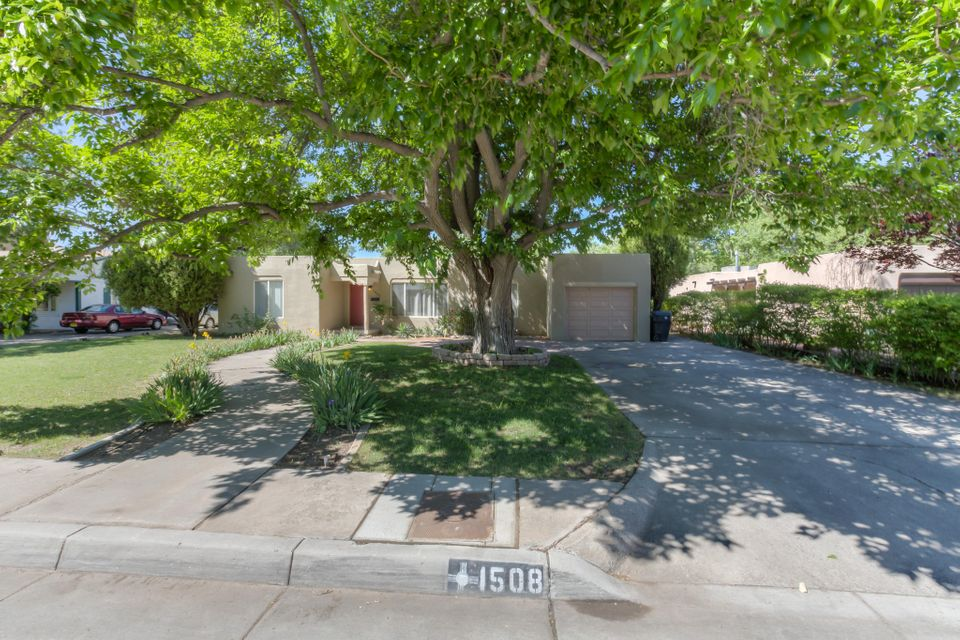 A Fantastic find in the Albuquerque Country Club Area! 3 Living Rooms offers a variety of ideas and flexibility! Granite Countertops, Laminate Wood Floors, & Stainless Steel Appliances.3 French Door Openings to U-Shaped Flagstone Patio Brings in abundance of natural of Light.Family Room Opens to Kitchen & Has a Beamed, Tongue&Groove Ceiling.Built in Shelving. Cove Ceilings in Living Room and Formal Dining Room. Great Home for Entertainers - Stunning Backyard with a flagstone patio featuring a killer Bar Top for Entertaining, an 18 X 12 Storage Building with electricity, Raised flower beds, and a spacious open patio. Plus a 3.5 KW Solar Panel sytem for energy savings. Ok...stop reading and schedule your showing!