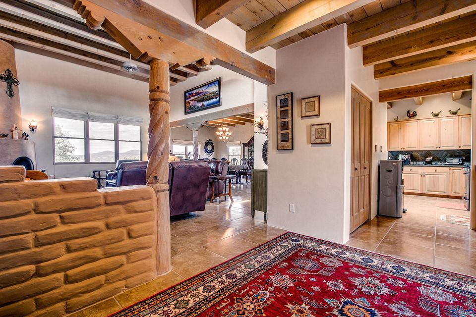 Beautiful SW Style home with tons of character! Wood beams and ceilings, vigas, wood windows, decorative tile lined skylights, beautiful maple cabinetry throughout, granite countertops in super spacious kitchen and baths! Stainless steel appliances, TONS of cabs and natural light! Kiva fireplaces, pellet stove in HUGE dining room! A TRUE MASTER SUITE! SO SPACIOUS!  Bring on the California KING! Full master bath, huge walk in closet, copper sinks, jetted tub, kiva fireplace, fantastic floor plan! Beautiful neutral tile flooring throughout, venetian plaster walls, very spacious and tons of storage! 2015; refi air, TPO roof,Awesome meadow and mountain views! 3 car garage plus detached workshop! Terrific and super convenient location! Horses allowed, NO HOA!