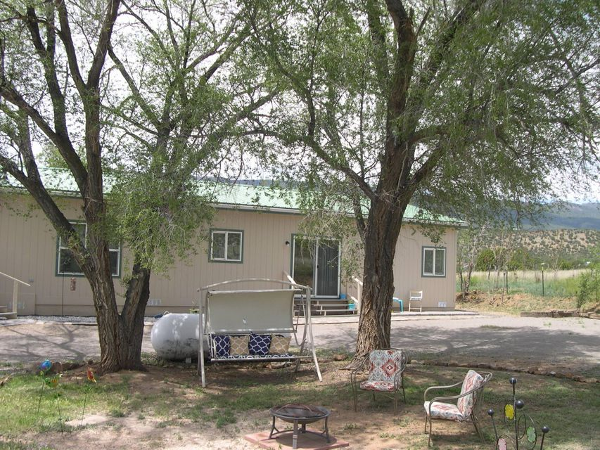 Beautiful 4BR Home in the convenient Village of Tijeras, less than 8 minutes to Tramway. Check the pictures! Certain to delight your most discriminating buyers. Home has custom features such as 9 foot ceilings, hardwood cabinets, architectural flourishes, 6 inch window ledges, and plant shelves. New paint inside and out, new carpet/tile, steel pro-panel roofing, 2 x 6 construction, newly fenced and gated. Good well, plus Village water system at street. Huge owner's suite features jetted tub, separate shower enclosure and an enormous walk-in closet, plus separation from other 3 bedrooms, which all feature walk-in closets. Lots of interior storage. Great room/formal living room flows into large dining area. Spacious kitchen with loads of storage including walk-in pantry, work-island and bar.