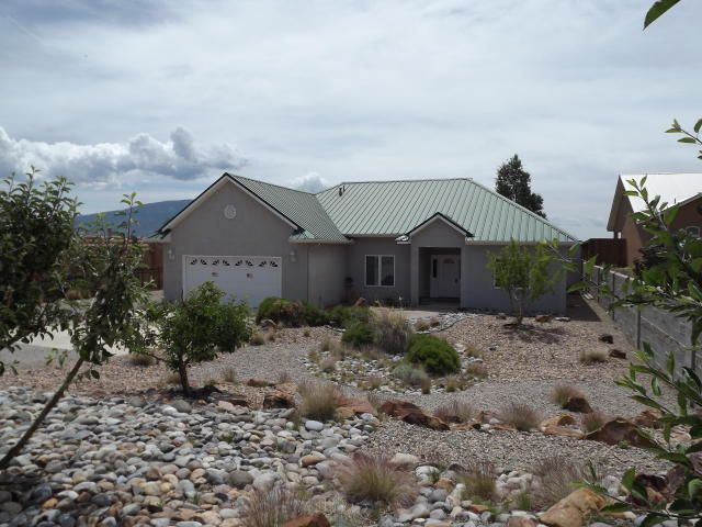 Custom home in Vista Entrada! Beautiful views of the Sandia Mts. on a 1/2 acre. Large master with soaker tub, walk in shower and outside access to small pool/spa and patio. Two living areas and 2nd bedroom has desk/sitting area with built-in cabinets. Over sized pantry and storage in laundry room, marble tile floors in entry and all wet areas. Many upgrades including heavy gauge metal roof, seamless gutters, inside walls insulated for sound, over sized garage, gas fire place and parking for your RV/toys. This is a must see home and neighborhood!  House proud owner and well taken care of. Refrigerator and surround sound system/speakers do not convey.