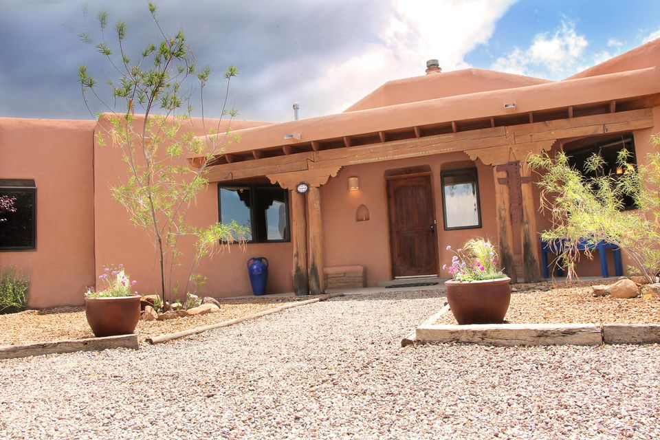 Immaculate single level home that has the charm of traditional New Mexican architecture. This 4 bedroom beauty is perfectly situated on a delightful .89 acre lot that is flooded with views.  Relax on the east covered portal and soak in the stunning views of the Sandia Mountains. This light filled home offers beautiful Vigas, Diamond Plaster Kiva FP, bright Kitchen w/Quartz Countertops, 2 Pantries, Breakfast Nook, 4th Bedroom has Private Courtyard Entry, Huge Master w/Kiva FP, Dbl Vanity, Jetted Tub, Separate Shower,2 Walk-In Closets & Mtn Views!-Wood Windows, Wood Interior Doors,Newer 95% efficiency Furnace, Tankless Hot Water Heater & Refrigerated Air! Bring the Horses! This home also features a 2 stall Barn, with plenty of storage and a cellar.