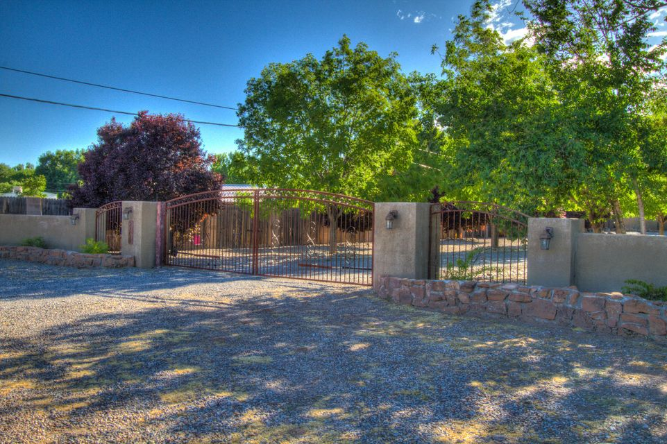 Private, secluded and peaceful retreat on almost an acre in the heart of Los Ranchos!  Stunning courtyard with fireplace leads to the rotunda entry.  Open northern New Mexico style great room with walls of French doors highlighting the beautiful views of the lush backyard, filled with colorful roses and fruit trees.  Backyard also has an amazing gazebo, and water rights.  The kitchen is a chef's delight with gas range and a singing fridge!  Reclaimed wood from India used for the custom kitchen cabinets.  Custom built pantry/mud room with TONS of storage. Master tower with views of the sunrise and colorful Sandia Mountain at dusk.  Fabulous custom closet! HUGE jet tub for soaking under the moonlight. This is a must-see. Qualified buyers only.  Motivated seller will consider all offers!