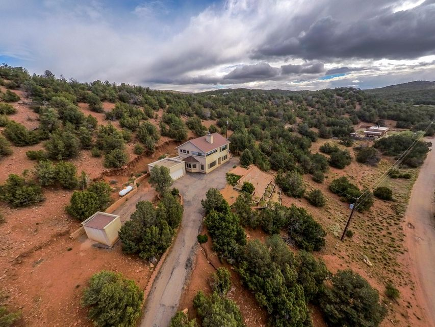 Imagine pulling in YOUR driveway to these MILLION Dollar views & realizing, '''Wow, we did it - we are truly living the good life!'' This amazing home feels like your very own mountain lodge! Great neighborhood w/ nearby access to miles of forest hiking & mountain biking trails. Sauna & Workout room on the upper level! Nestled among mature trees. Bright Open floor plan! Home is set-back from the road & offers total privacy, embracing the beautiful surroundings. Only moments to ABQ, yet worlds apart. Nestled In The Sandia Mountains Just Minutes From Alb! Wonderful Views! Ton's Of Trees! 4 Acres Of Peaceful Forest! Large Family Room w/Fireplace! Chef's Delight Kitchen! Talk about LOCATION, LOCATION, LOCATION!!!!