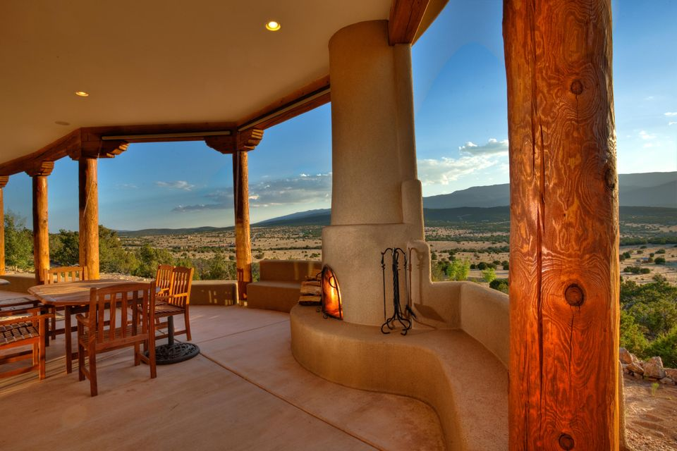 Perched on a hill top on 10+ acres in San Pedro Creek Estates this custom pueblo style home will leave you in awe! Expansive views of the Sandia & Jemez mountains are captured perfectly throughout the home & outside covered portals. The gourmet kitchen has granite counter tops, SS appliances, Wolf 6-burner, kitchen island, pantry & ample cabinetry. Master suite is a luxurious retreat w/ its private portal perfect for watching sunrises & sunsets over the Sandia's & huge custom walk-in closet w/ adjacent laundry rm. Master bath features his/her sinks, large walk-in snail shower, & pedestal soaking tub. High viga tongue & groove ceilings , nichos, along with gleaming colored concrete floors throughout. Energy efficient w/solar hot water system. This 4 bedroom 4 bath home is truly a must see!