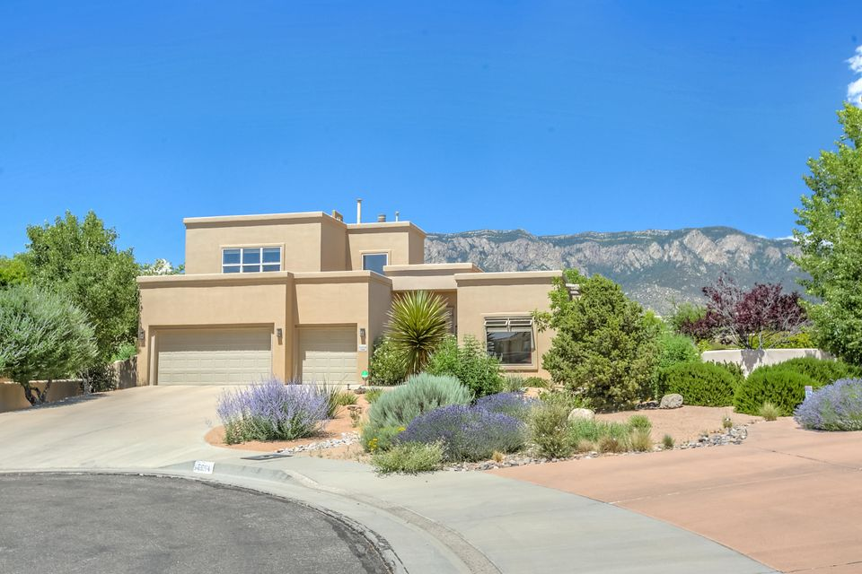 Beautiful Modern Pueblo home in the desirable High Desert neighborhood. Stunning interior remodel by renowned designer Susan Westbrook. Gorgeous kitchen with new stainless steel appliances, induction cook top, custom Mexican tile, and sandstone countertops. Living space features towering ceilings, dark wood beams, & panoramic views of the Sandias. Luxurious flagstone flooring with radiant heating & lower level master suite. Freshly redesigned landscape with a spacious & partially covered courtyard, perfect for relaxing & entertaining. New cooling system, Puronics NASA-tech water softener, water heater, & rooftop deck built with hassle-free composite. Newly serviced roof & spacious three-car garage with additional refrigerator & abundant storage