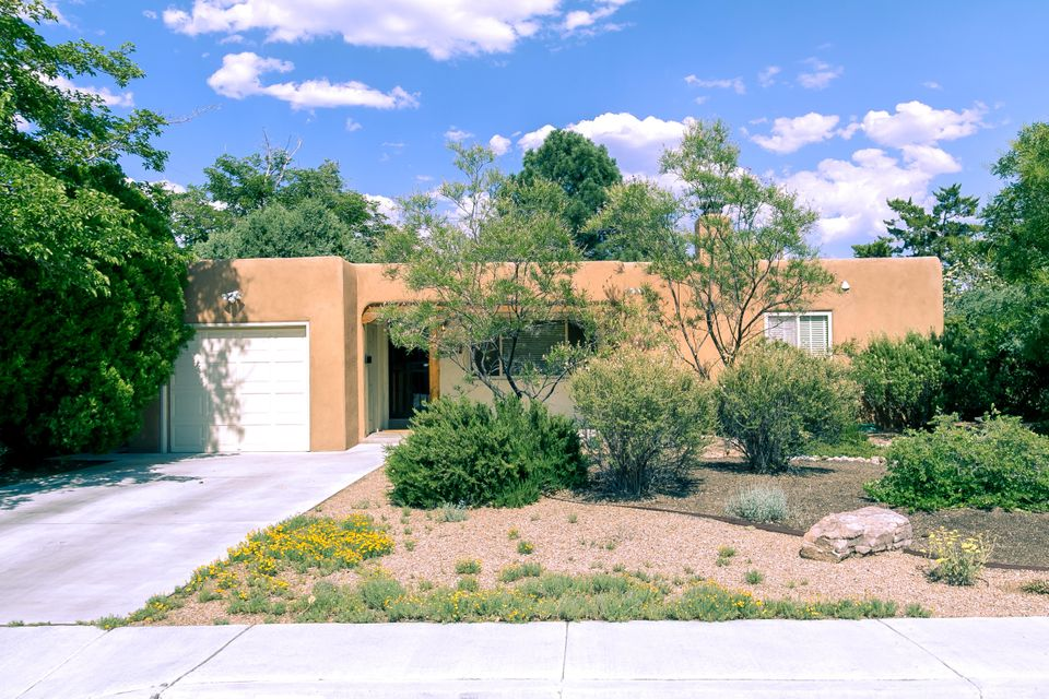 A nearly perfect combination of vintage and modern + elegant and casual yet totally comfortable, livable and wonderful! Superbly maintained UNM area Pueblo-style casa with easy access to law/med schools, golf and Nob Hill. Classic touches such as hardwood floors, coved ceilings and fireplace + awesome remodeled kitchen with gorgeous granite counters & stainless-steel appliances (fridge stays!). Large living room, formal dining room, three bedrooms and one and one-half baths. Laundry room (washer/dryer stay!). Oversized one-car garage. Welcoming front porch, open patio in back and beautifully landscaped all around. An amazing house in a popular location.